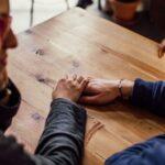 Par holder hånd ved bord