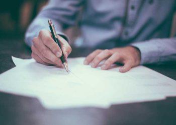 Mand der skriver på papir